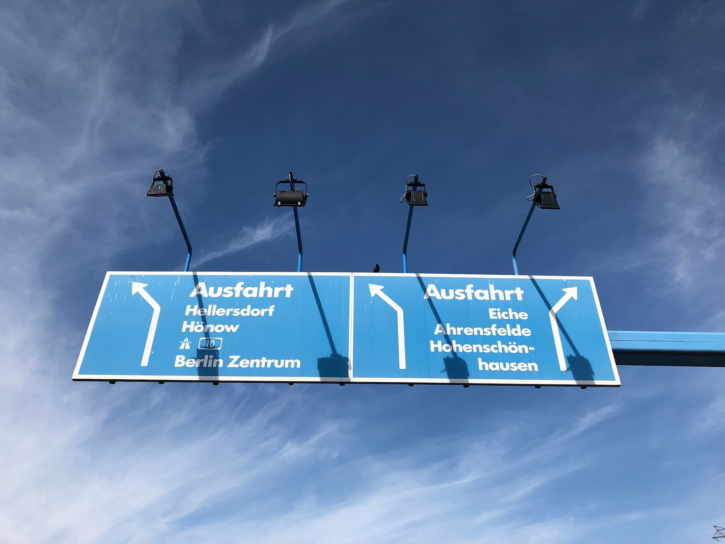 Front angle: Blue street sign showing direction in white letters with lights creating shadows on the surface and dark-blue sky with soft clouds