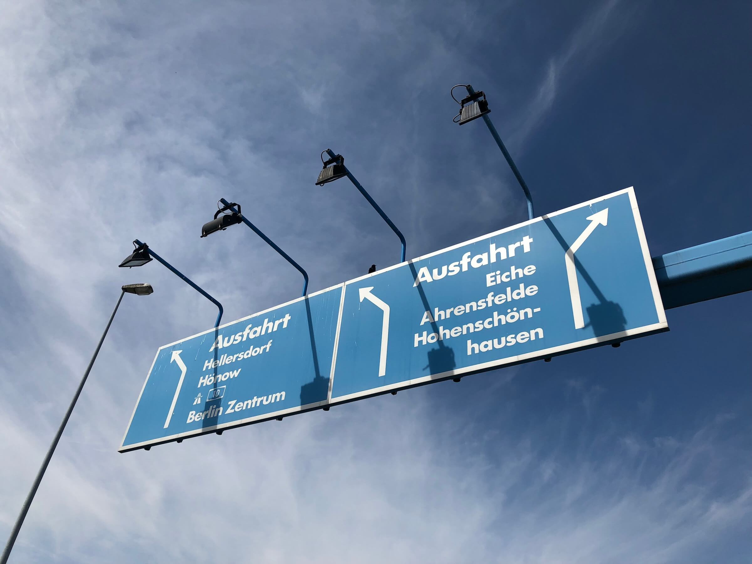 Side angle: Blue street sign showing direction in white letters with lights creating shadows on the surface and dark-blue sky with soft clouds